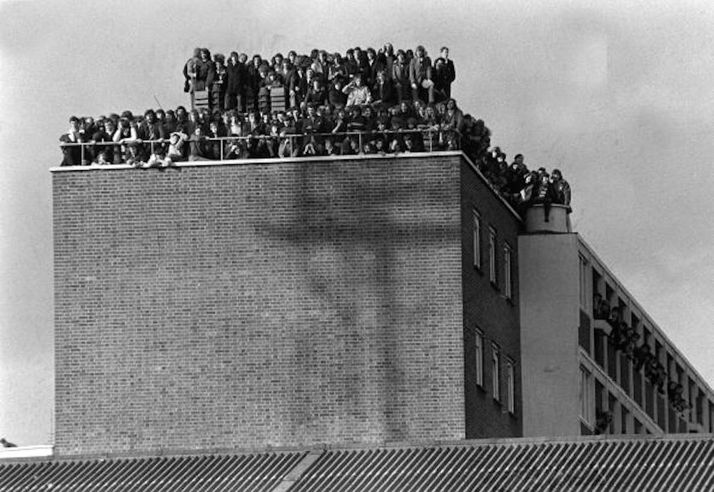 Sport, Football, London, England, 14th February 1972, Fans crowd the roof of a block of flats overlooking West Ham's Upton Park pitch as the Hammers win their FA Cup replay v Hereford 3-1  (Photo by Popperfoto/Getty Images)