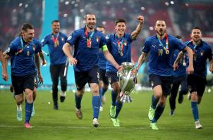 Italy's Giorgio Chiellini and Leonardo Bonucci carry the trophy and celebrate with team-mates after winning the penalty shoot-out after the UEFA Euro 2020 Final at Wembley Stadium, London. Picture date: Sunday July 11, 2021.